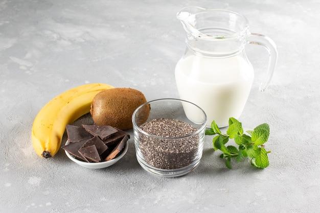 灰色のテーブルにバナナとキウイを使ったチョコレートチアプディングを作るための材料