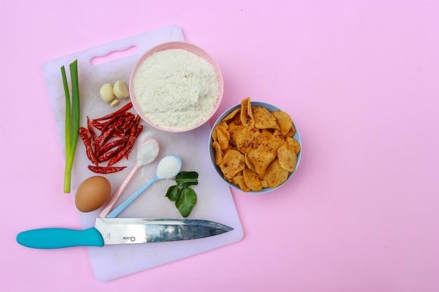 파스텔 핑크 배경으로 맛있는 매운 인도네시아 스낵을 만들기 위한 재료