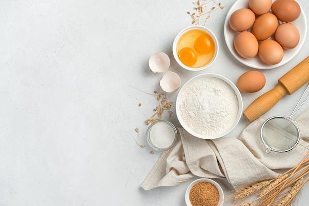 반죽 요리를 만들기 위한 재료: 케이크, 쿠키, 피자, 회색 배경에 파스타. 밀가루, 계란, 설탕. 상위 뷰, 복사 공간입니다.
