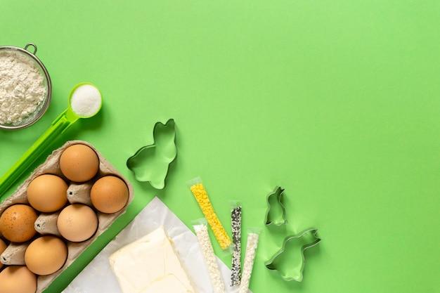 緑の背景、コピースペースにバニーの形をしたイースタークッキーを作るための成分。