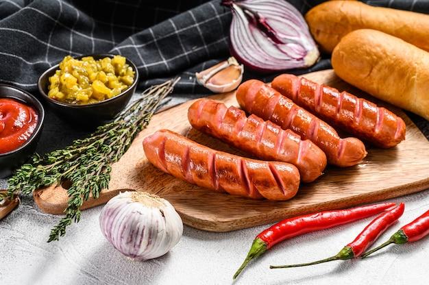 Ингредиенты для приготовления домашних хот-догов. колбаски, свежие печеные булочки, горчица, кетчуп, огурцы. вид сверху