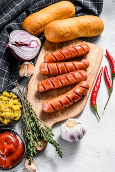 Ингредиенты для приготовления домашних хот-догов. колбаски, свежие печеные булочки, горчица, кетчуп, огурцы. белый фон. вид сверху