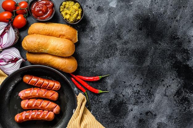 Ингредиенты для приготовления домашних хот-догов. колбаски в сковороде, свежие печеные булочки, горчица, кетчуп, огурцы. черный фон. вид сверху. копировать пространство