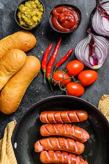 Ингредиенты для приготовления домашних хот-догов. колбаски в сковороде, свежие печеные булочки, горчица, кетчуп, огурцы. черный фон. вид сверху