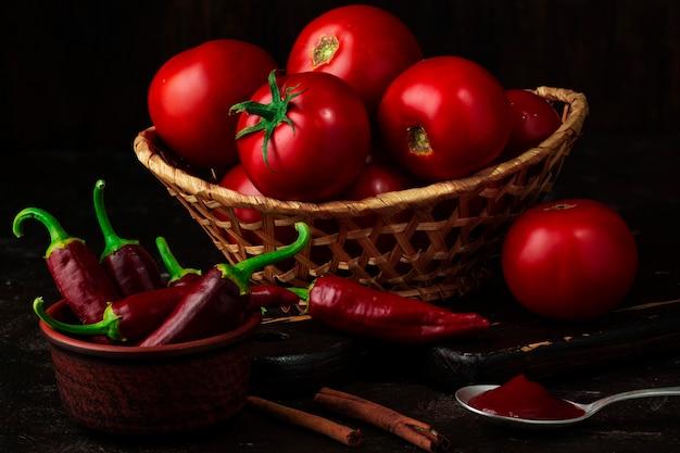 Ингредиенты для приготовления кетчупа. корзина помидоров, острого перца, корицы и ложки кетчупа.