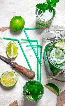 Ингредиенты для приготовления мохито - лайм, листья мяты, ром, нож для цитрусовых и старый стол. вид сверху