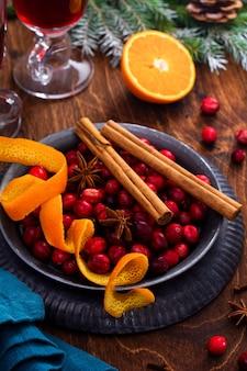 Ингредиенты для приготовления глинтвейна с клюквой. апельсин, корица, ягоды клюквы, гвоздика, анис и сахар. рождественские атмосферные ретро концепции. место для текста