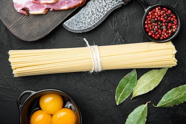 Ингредиенты для приготовления пасты alla carbonara прошутто, набор сырых макарон, на черном камне