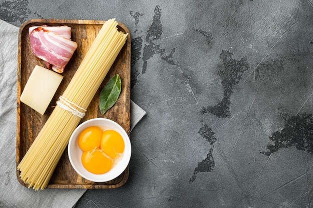 Ингредиенты для приготовления пасты alla carbonara прошутто, набор сырых макарон, на сером камне