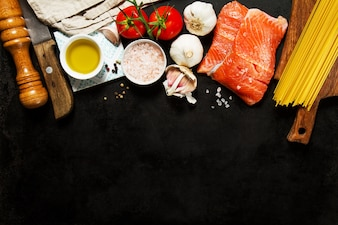 Ingredients for making pasta and salmon fillets on a wooden board