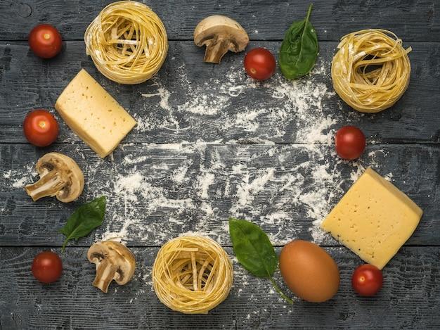 Ингредиенты для приготовления пасты с грибами и помидорами на деревянном фоне. место для текста. ингредиенты для приготовления макаронных изделий.