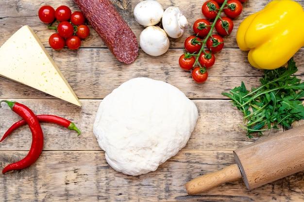 Ингредиенты для приготовления пиццы, перед выпечкой, на деревянном столе, вид сверху, пошаговый рецепт