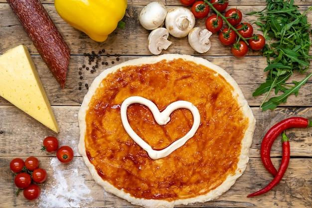焼く前に、木製のテーブルでピザを作るための材料、上面図、ステップバイステップのレシピ