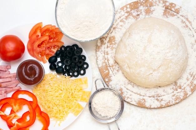 白い背景の上にピザを作るための材料。イタリア料理。チーズ、トマト、ピザ生地、小麦粉、ソース、オリーブなど
