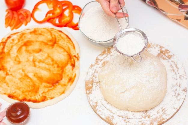 白い背景の上にピザを作るための材料。イタリア料理。料理人は生地に小麦粉を振りかける。チーズ、トマト、ピザ生地、小麦粉、ソース、オリーブなど