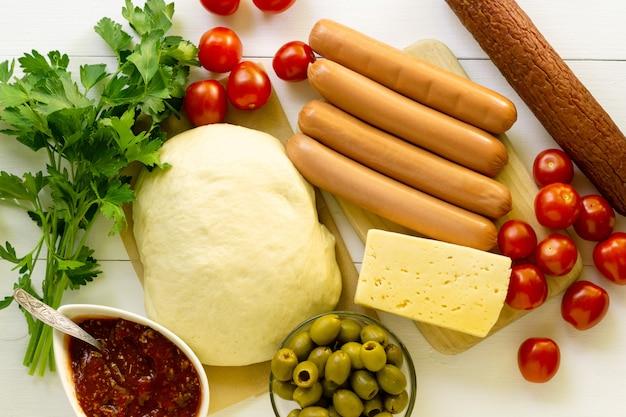 Ингредиенты для приготовления колбасы пиццы на белом фоне деревянные