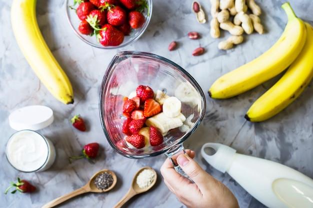 회색 테이블에 딸기 바나나 스무디를 만들기위한 재료 프리미엄 사진