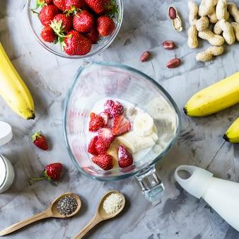 회색 테이블에 딸기 바나나 스무디를 만들기위한 재료