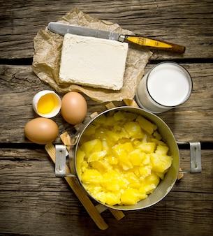 Ингредиенты для пюре - яйца, молоко, масло и картофель на деревянном фоне