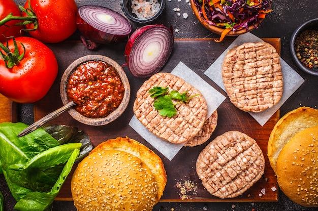 Ингредиенты для мясных гамбургеров с овощами и салатом из капусты на темном фоне, вид сверху, копией пространства.