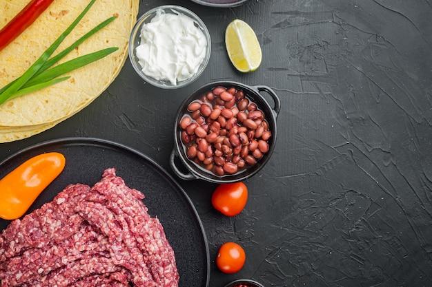 Ингредиенты для мексиканской кесадильи с соусом сальса, на черном фоне