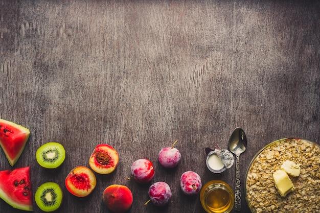 暗い木製のテーブルのオートミールの材料。健康食品の概念。上面図、コピースペース。フラットレイ。静物。トーン