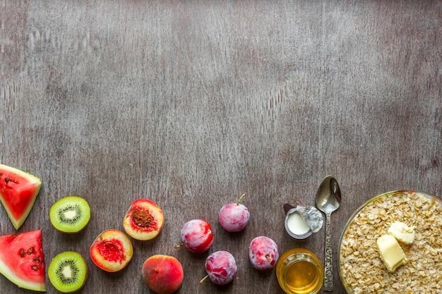 暗い木製のテーブルのオートミールの材料。健康食品の概念。上面図、コピースペース。フラットレイ。静物。