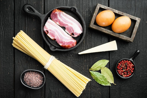 Ингредиенты для макаронных изделий карбонара. набор традиционных итальянских блюд, на черном деревянном столе, плоская планировка, вид сверху