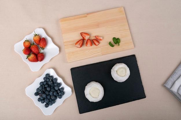 Ингредиенты для торта павлова: клубника, черника и безе. вид сверху.