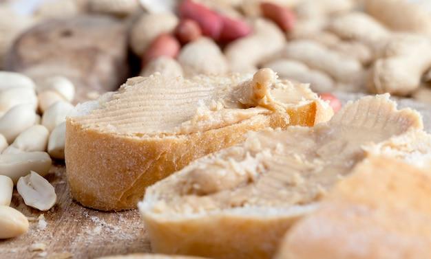 パンとピーナッツの簡単な朝食を準備するための材料、テーブルの上のおいしいピーナッツバターと白パン、クローズアップピーナッツペーストとローストピーナッツ