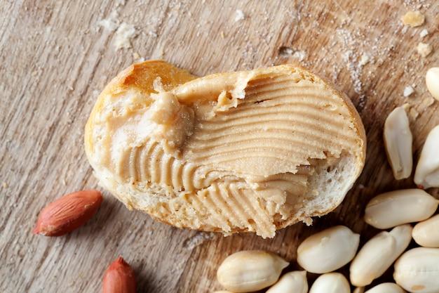 パンとピーナッツの簡単な朝食を準備するための材料、ピーナッツペーストのローストピーナッツ、おいしいピーナッツバターとテーブルの上の白パン、クローズアップ
