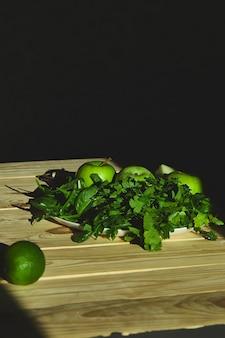 緑のデトックススムージーを準備するための材料、新鮮な果物と緑のほうれん草で健康的なスムージーを調理します。ライフスタイルのデトックスコンセプト。ビーガンドリンク。