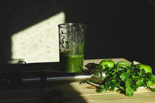 緑のデトックススムージーをブレンダーで準備し、健康的なスムージーを新鮮な果物とほうれん草で調理するための材料。ライフスタイルのデトックスコンセプト。ビーガンドリンク。