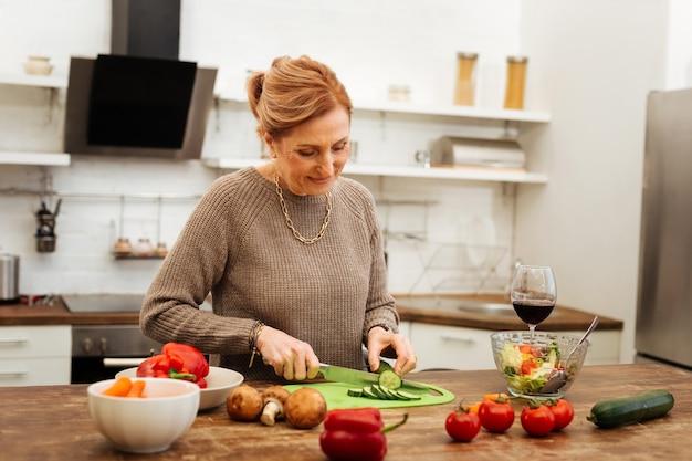 サラダの材料。キッチンに滞在し、夕食のために新鮮な野菜を切る金の宝石類の集中した楽しい女性