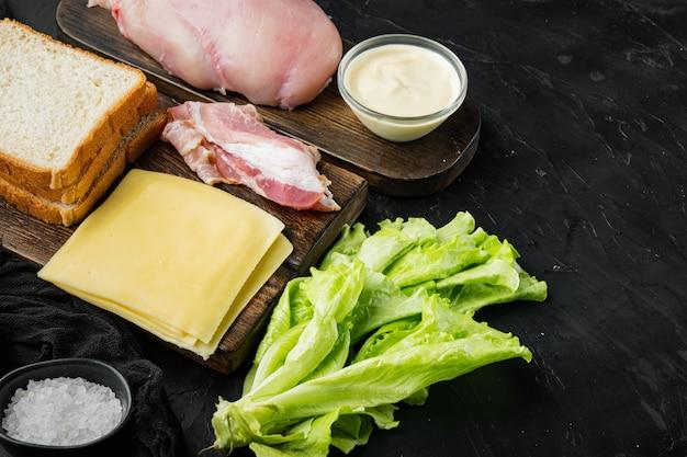텍스트 복사 공간이 검은 배경에 샌드위치, 베이컨, 치즈, 토마토, 닭고기, 양상추, 소스 재료