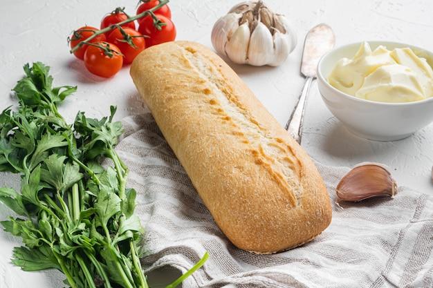 흰색 돌 테이블 배경에 버터, 허브, 바게트 세트를 넣은 샌드위치 재료