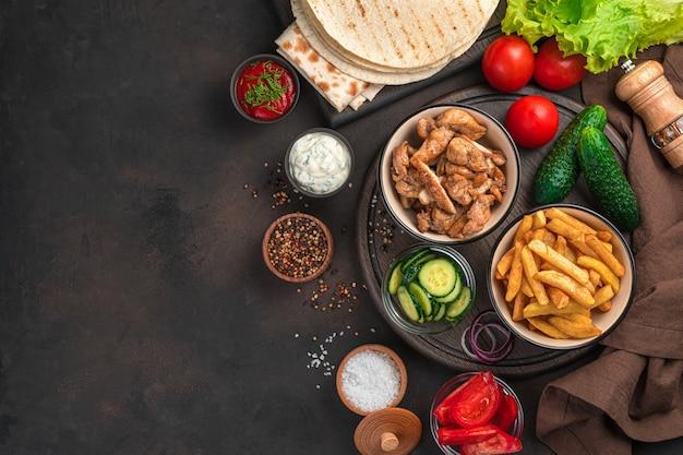 Ингредиенты для шаурмы, буррито, гироса или полноценного обеда из картофеля фри, жареной курицы и овощей. вид сверху, копия пространства.