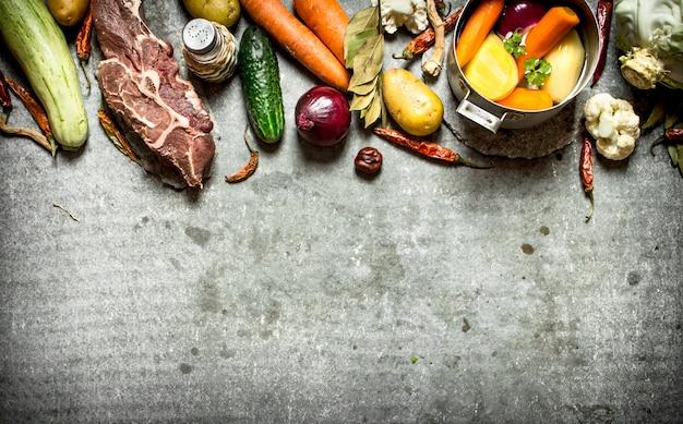 Ингредиенты для супа с овощами, специями и мясом. на каменном столе.