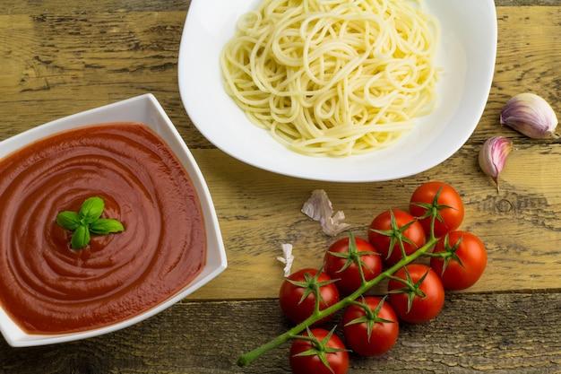 木製テーブルのスパゲッティ、トマトソース、パスタ、トマトの材料