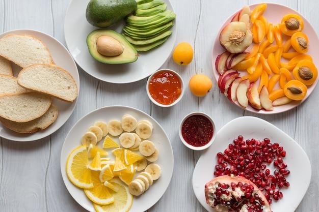흰색 나무 테이블 위에 빵과 다양한 과일 살구, 석류, 복숭아, 아보카도, 오렌지, 바나나의 달콤한 토스트 조각 재료