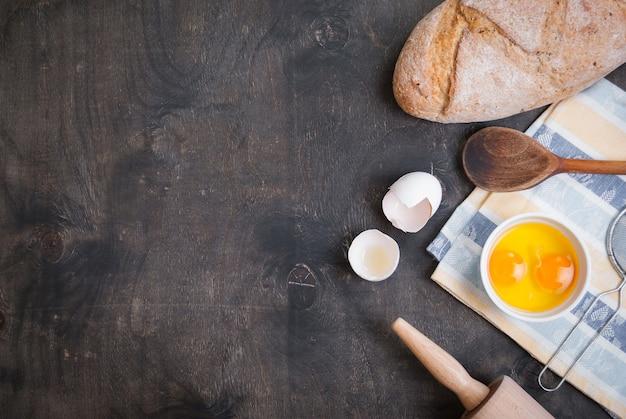 Ингредиенты для выпечки, яичная скорлупа, хлеб, мука и скалка на черном фоне стола