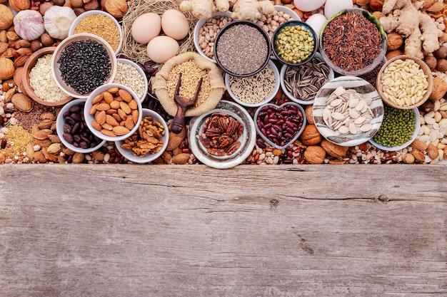 セラミックボウルの健康食品選択のための成分。コピースペースと白いぼろぼろの木製の背景に設定されたスーパーフードのコンセプト。