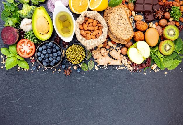 건강 식품 선택을위한 재료는 어두운 돌 배경에 설정합니다.