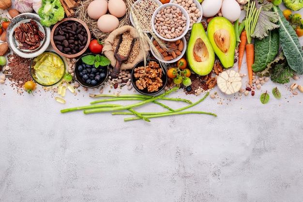 健康食品の選択のための成分。コピースペースと白いぼろぼろのコンクリートの背景に設定されたスーパーフードの概念。
