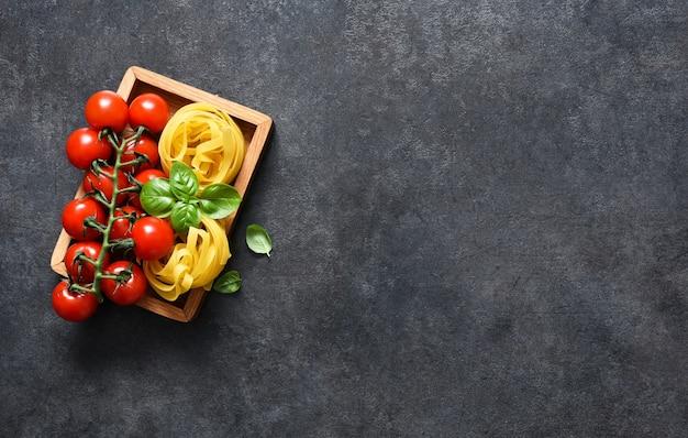 Ингредиенты для макаронных изделий. паста тальятелле, помидоры и базилик на черном бетоне