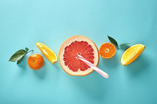 Ингредиенты для приготовления свежевыжатых соков и смузи из апельсинов, мандарина и грейпфрута выложены в ряд на синем фоне плоской планировкой.