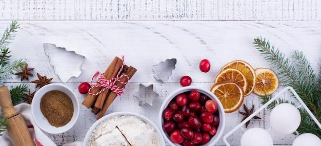 明るい木の背景に自家製のクリスマスベーキングクランベリー、小麦粉、シナモン、卵、調味料アニスを準備するための材料。上面図