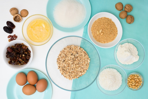 Ингредиенты по рецептуре домашнее овсяное печенье с финиками, арахис, кокосовая стружка, яйца, мука, соль в глазированных тарелках на светлом фоне.