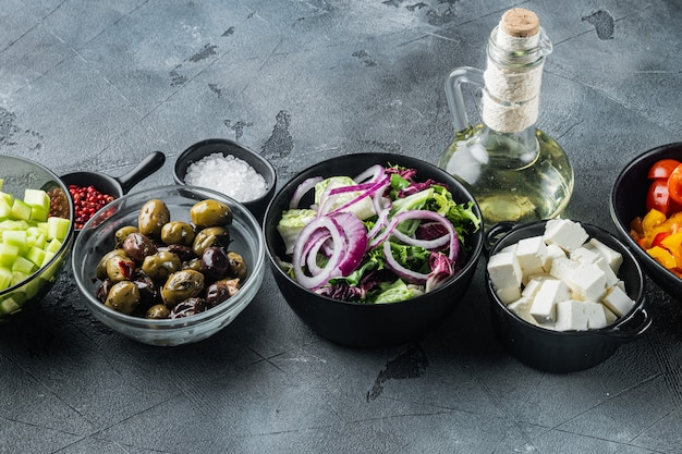 Ингредиенты для традиционного греческого салата. помидоры, лук, оливки, сыр фета, на сером столе