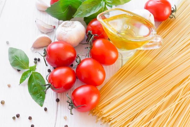 전통적인 이탈리아 파스타 스파게티, 토마토, 바질과 올리브 오일 선택적 포커스 복사 공간에 대 한 재료.